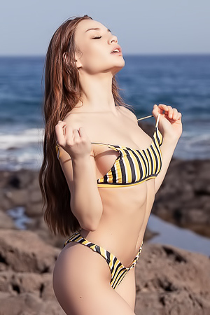 Clara removes her striped bikini on a rocky beach
