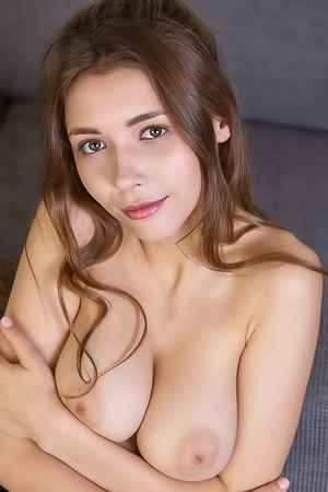 Mila Azul Sitting With Slender Thighs Parted To Expose Her Shaved Pussy